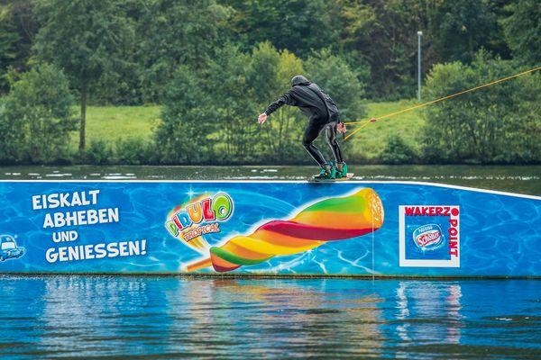 Der Wakeboarder gleitet über die Rampe im Wasser