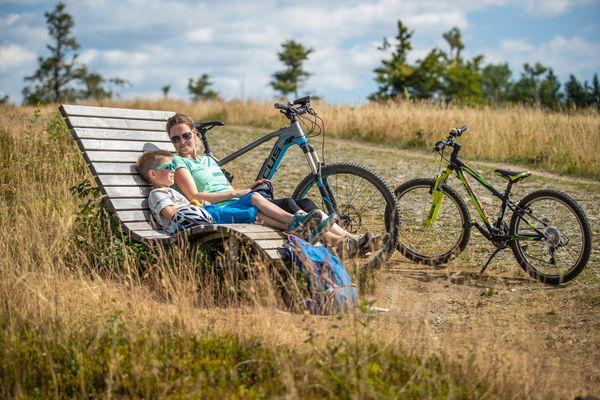 Zwei E-Mountainbiker sitzen auf einer Bank und machen eine Pause. Ihre Fahrräder stehen neben der Bank.