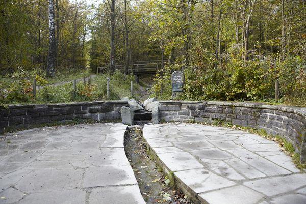 Quelle mit Steinmauer und Rinnsal im Boden