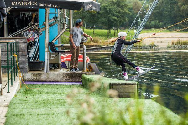 Eine Frau springt gerade von der Holzplattform ab für den Start